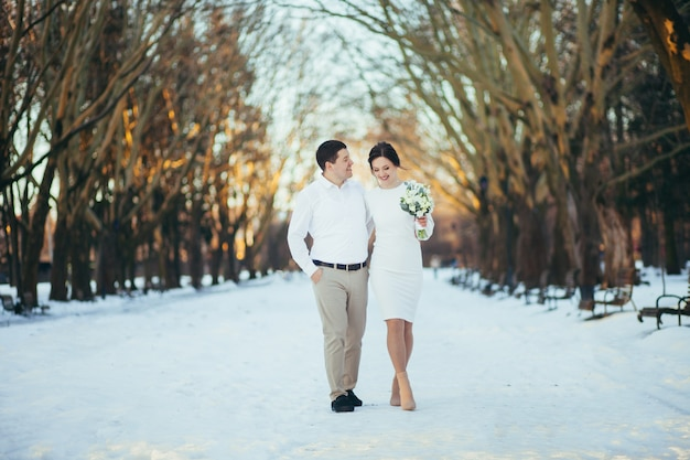 Young married couple walks in winter park on christmas day