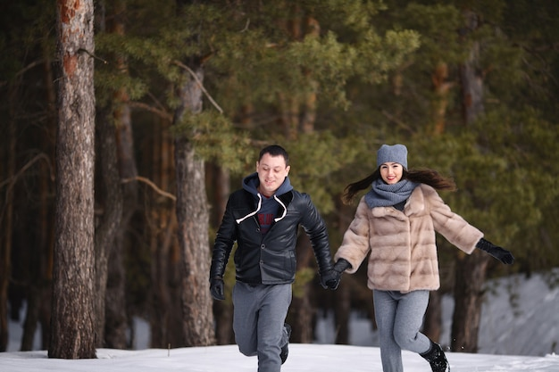 Young married couple in winter in a snowy forest hold hands