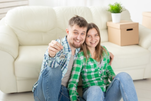 Молодая супружеская пара с коробками и плоскими ключами.