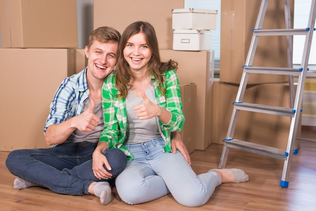 Young married couple with boxes and holding flat keys