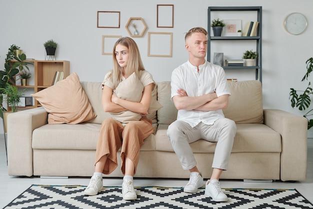 팔짱을 끼고 화난 표정을 한 젊은 부부는 다툼이나 말다툼 후에 소파에 앉아 침묵을 지킨다