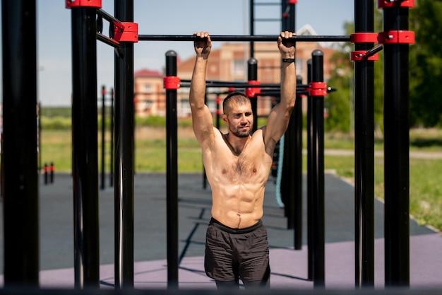 スポーツグラウンドに立ちながらスポーツ施設のバーで保持している男性の胴体を持つ若い男性アスリート