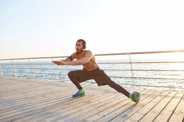 Young masculine sporty bearded guy doing stretching, listening to favorite music on headphones, morning exercises by the sea, warm-up after running.