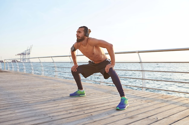 Young masculine sporty bearded guy doing stretching, morning exercises by the sea, listening favorite music on headphones, warm-up after run, leads healthy active lifestyle. fitness male model.