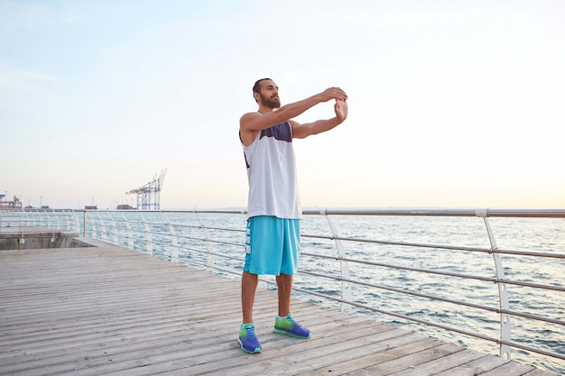 Young masculine sporty bearded guy doing stretching, morning exercises by the sea, warm-up after run, leads healthy active lifestyle. fitness male model.