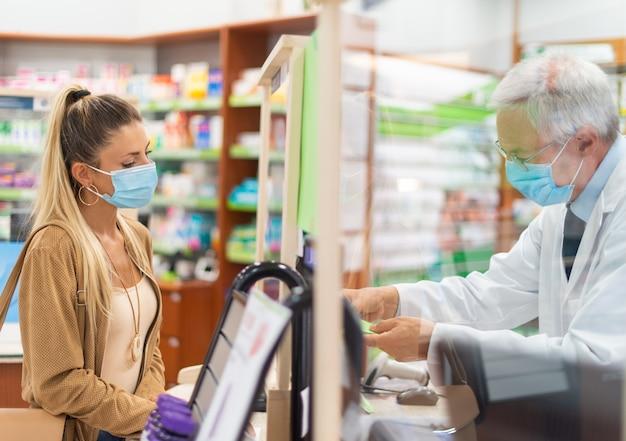 薬局でチェックアウトする若い仮面の女性、コロナウイルスの概念