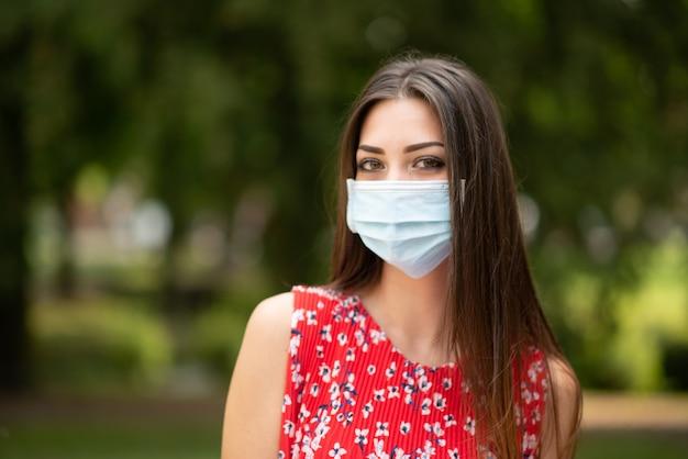 Молодая женщина в маске в парке