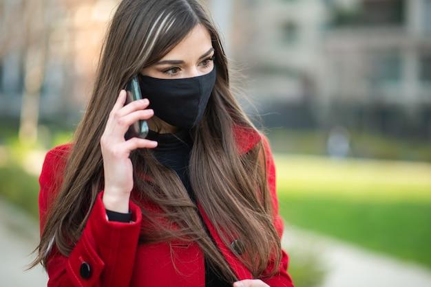電話で話している若い仮面の女性、covidとコロナウイルスのコミュニケーションの概念