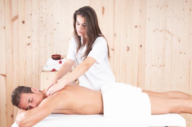 Молодой массажист лечит мускулистого парня