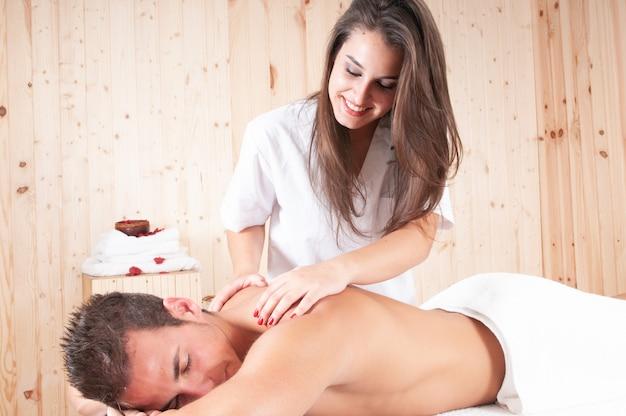 筋肉質の男に治療を適用する若いマッサージ師