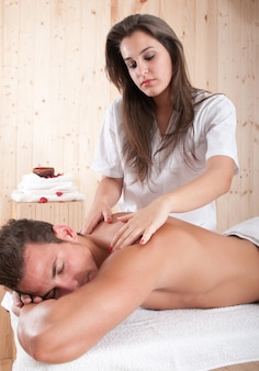 Young masseur applying a treatment to a muscular guy