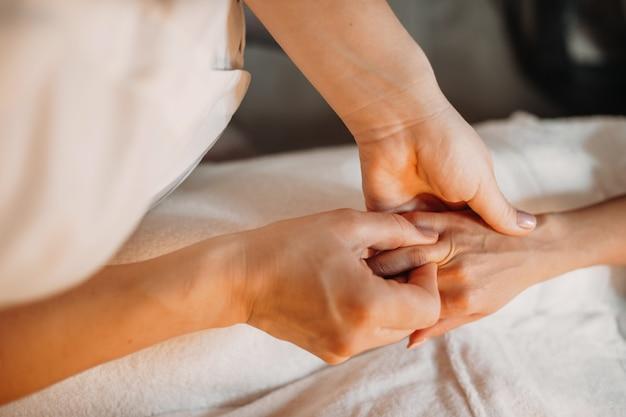 若いマッサージ師は、スパセッションの後にリラックスするために女性の指をマッサージしています