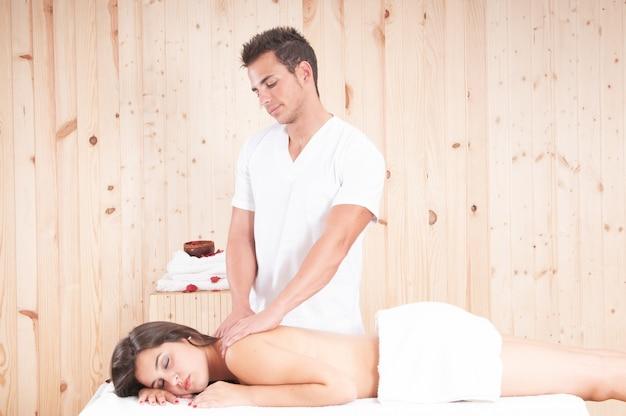 Молодая массажистка лечит девушку
