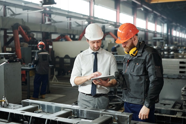 공장 작업장에서 태블릿 디스플레이에 대한 기술 스케치를 논의하는 안전모와 수염 난 엔지니어의 젊은 마스터