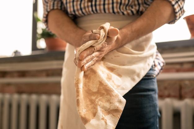 若き陶芸の達人が生の粘土を加工してワークショップで練った後、エプロンで手を拭きます