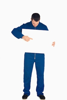 Young mechanic in boiler suit pointing on banner in his hands