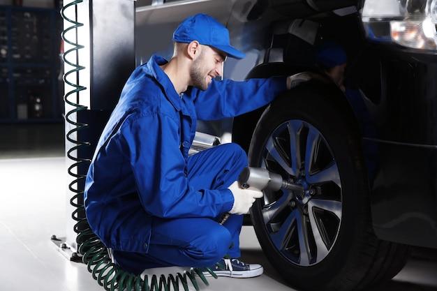 Молодой механик, меняющий колесо в автосервисе