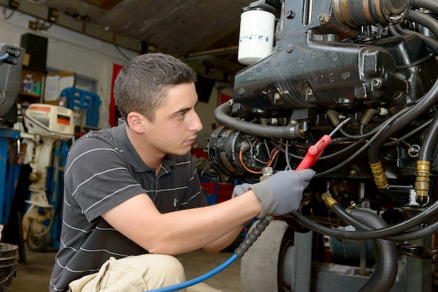 Young mechanic cleans the engine with compressed air