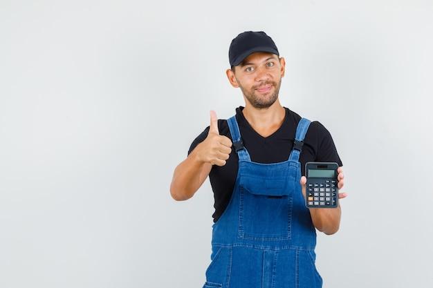 Молодой механик в униформе, держа калькулятор с большим пальцем вверх и выглядящий веселым, вид спереди.