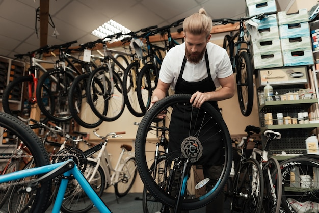 Young mechanic repairs bicycle in bike workshop.