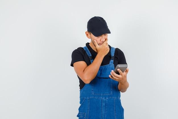 Giovane meccanico in uniforme tenendo la calcolatrice con la mano sulla bocca e guardando pensieroso, vista frontale.