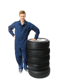 Young mechanic in uniform with wheels isolated