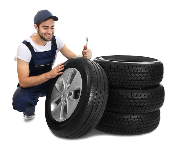 Young mechanic in uniform with wheels on white surface