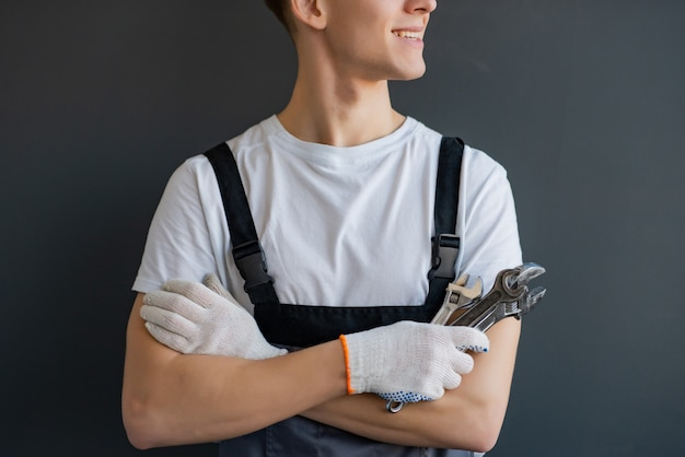 Young mechanic with crossed arms and wrench standing on gray background