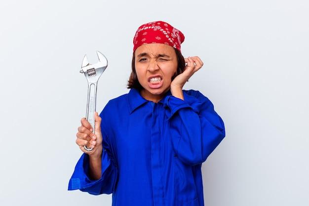 手で耳を覆う孤立したキーを保持している若い機械の女性。