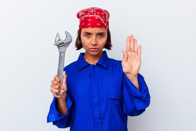 一時停止の標識を示す伸ばした手で孤立した立っているキーを保持している若い機械の女性は、あなたを防ぎます。