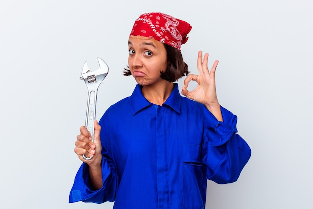 Young mechanical woman holding a key isolated cheerful and confident showing ok gesture.