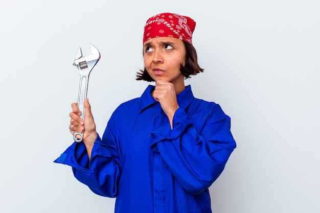 Young mechanical woman holding a key isolated looking sideways with doubtful and skeptical expression