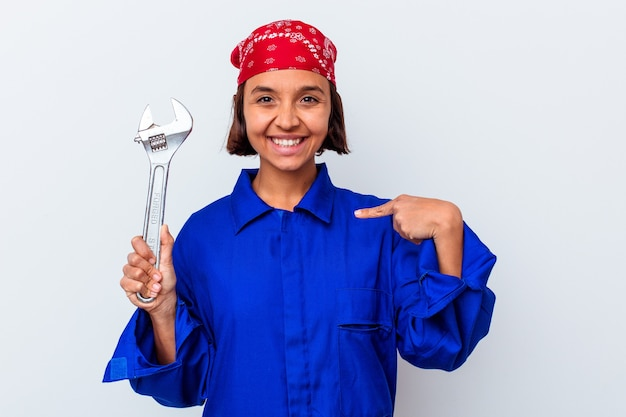 Young mechanical woman holding a key isolated person pointing by hand to a shirt copy space, proud and confident