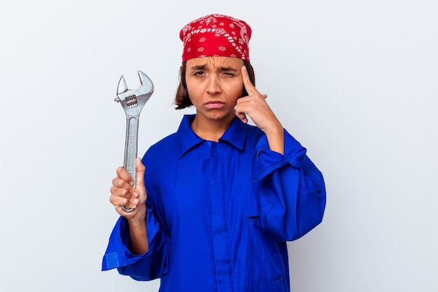 Young mechanical woman holding a key isolated pointing temple with finger, thinking, focused on a task.