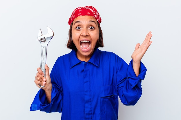 Young mechanical woman holding a key isolated receiving a pleasant surprise, excited and raising hands.