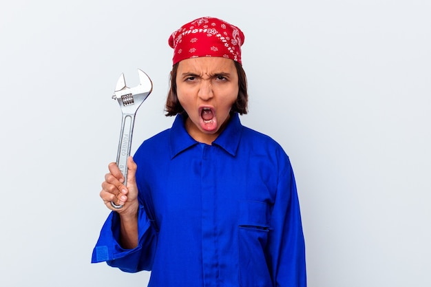 Young mechanical woman holding a key isolated screaming very angry and aggressive.