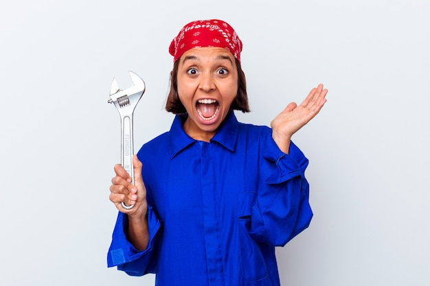 Young mechanical woman holding a key isolated surprised and shocked