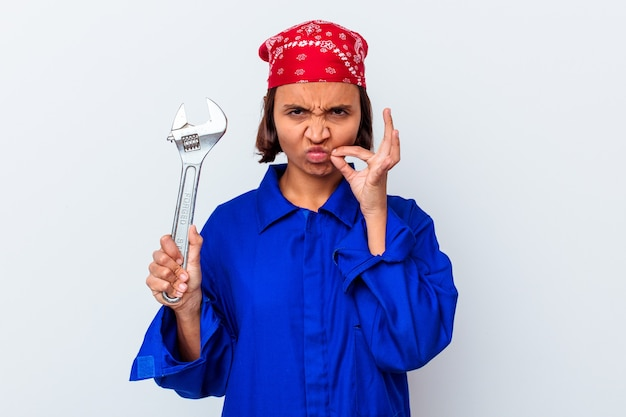 Young mechanical woman holding a key isolated with fingers on lips keeping a secret.