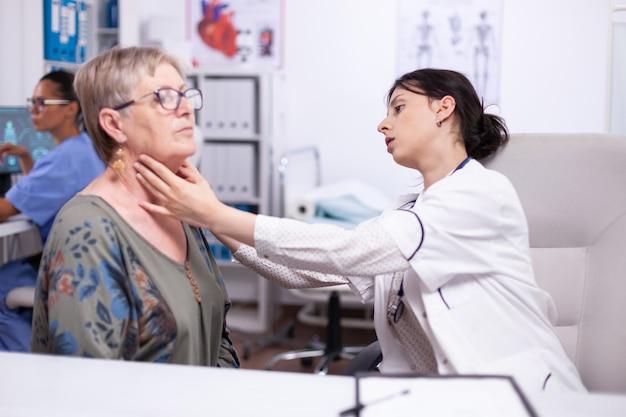年配の女性の若い薬用触診首、病院で医者を訪問している年配の患者がクリニックで健康に触れている甲状腺の喉をチェックしています。ヘルスケアの専門家、メディケア、治療医療の概念。