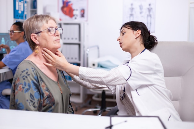 Young medic palpating neck of senior woman, elderly patient visiting doctor at hospital checking thyroid throat touching health at clinic. healthcare specialist, medicare, treatment medical concept.
