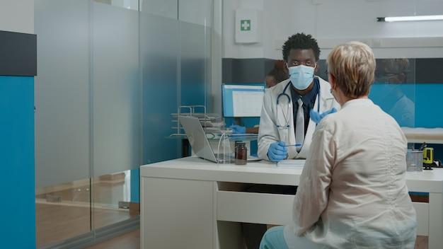 年配の患者に相談しながらフェイスマスクを身に着けている若い薬