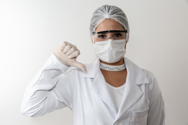 Young medical woman making thumbs down sign
