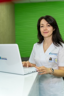 Young medical worker sitting at desk. female doctor with laptop smiling to camera in office.