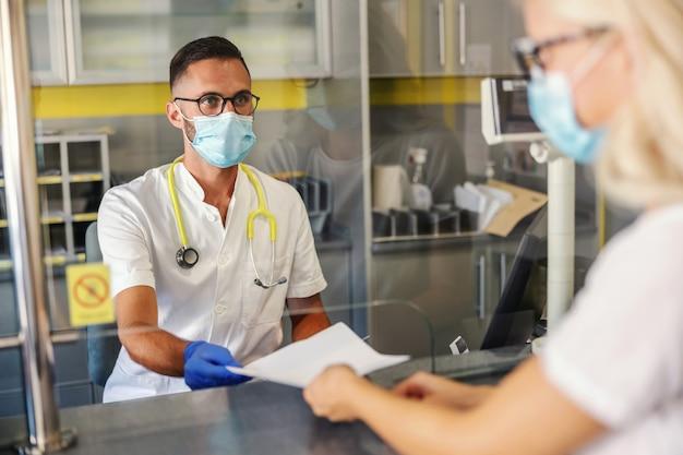 Молодой медицинский работник с резиновыми перчатками, маской для лица, в стерильной униформе дает результаты анализов пациенту, сидя в лаборатории.