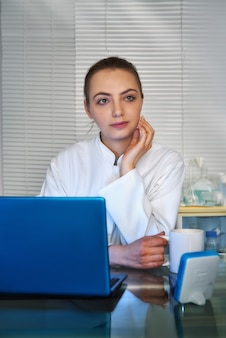 Young medtech, doctor or practitioner drinks coffee in front of working laptop