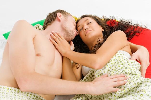 若い男性と彼の事件はベッドに横たわって一緒に抱きしめています