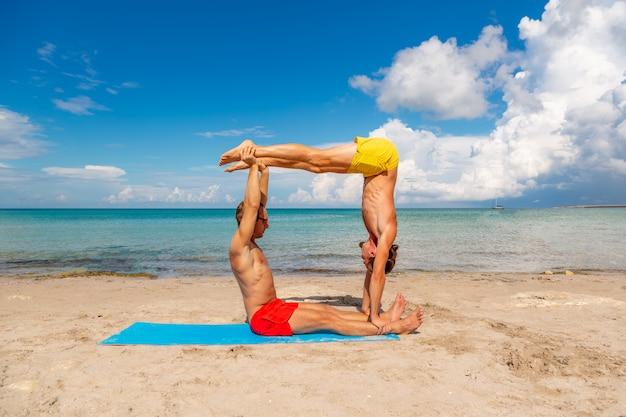 若い男性と女性のビーチでフィットネスヨガ運動を一緒にやっています。強さとバランスのアクロヨガ要素