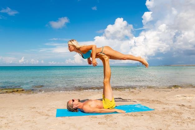 一緒にフィットネスヨガの練習をしているビーチで若い男性と女性
