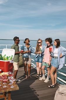 Молодые мужчины и женщины наслаждаются небольшой вечеринкой на деревянном пирсе, они пьют алкоголь и болтают