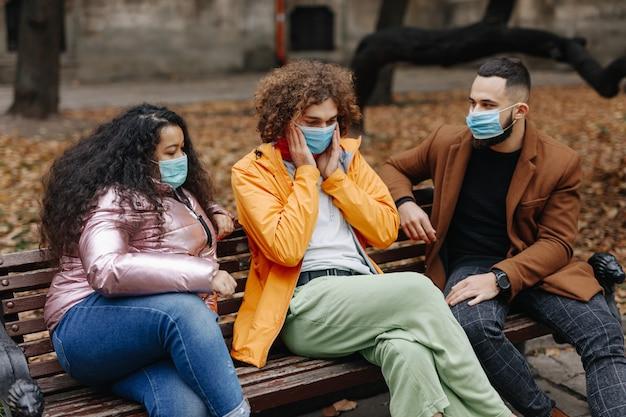 木製のベンチに一緒に座って、秋の公園で自由な時間を過ごす医療マスクの若い男性と女性。検疫中の友情の概念。